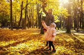 Young Mother And Little Daughter In Autumn Park Play With Yellow Leaves. Happy Weekend With Family I poster