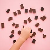 Closeup Of Kid Boy Hand Taking A Piece Of Chocolate From Pink Table Background With A Lot Of Pieces  poster