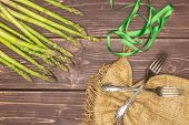 Set Of Lot Of Whole Fresh Green Asparagus Spear With Jute Cloth Flatlay On Brown Wood poster