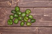 Lot Of Whole Fresh Green Mini Baby Kiwi Fruit Close To Each Other Flatlay On Brown Wood poster