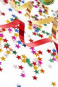 stock photo of reveillon  - red and golden ribbons and small confetti stars - JPG