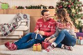 Husband And Wife Opening Christmas Presents And Looking At Each Other At Home poster