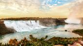 Panorama Of Golden Sunrise Over Niagara Falls Showing The Famous Waterfalls Of American Falls And Br poster