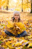 Autumn Portrait: Cute Smiling Little Girl Sitting On The Fallen Leaves In Autumn Park And Holding Th poster