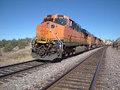pic of bnsf  - Freight train on two main tracks with an orange locomotive on a clear day - JPG