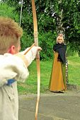 stock photo of longbow  - Rear View Of Archer Pointing Bow At Women With The Apple On The Head - JPG