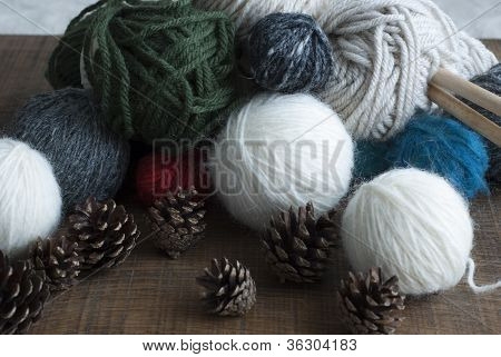 Balls Of Wool In Variety Of Colours With Wooden Knitting Needles And Fircones.