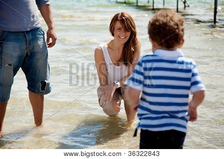 Mom Smiles As Her Son Walks Towards Her In The Water