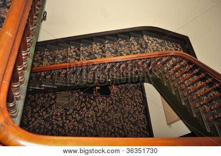 Stairwell With Wood Railing And Rug