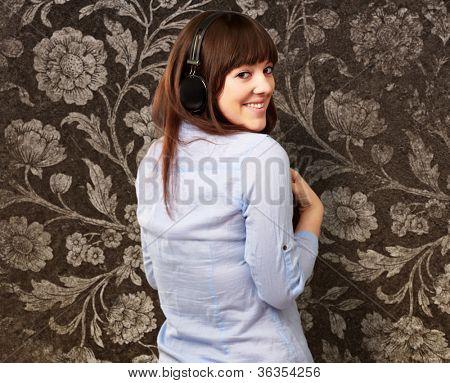 Happy Woman Wearing Headphone On Wallpaper