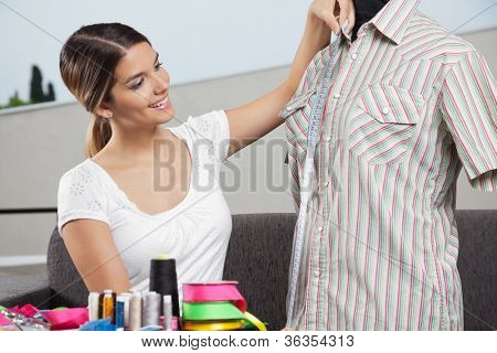 Young woman taking measurement of a shirt with dressmaking accessories in foreground