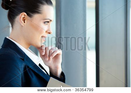 beautiful young businesswoman looking outside window