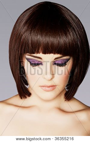 closeup portrait of beautiful young woman with short brown hair and dramatic eye makeup of purple eyeshadow and eyeliner .