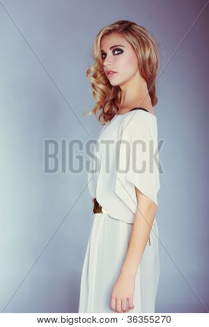 beautiful blond girl with curly long hair and smoky eyeshadow makeup in long white dress on blue studio background.