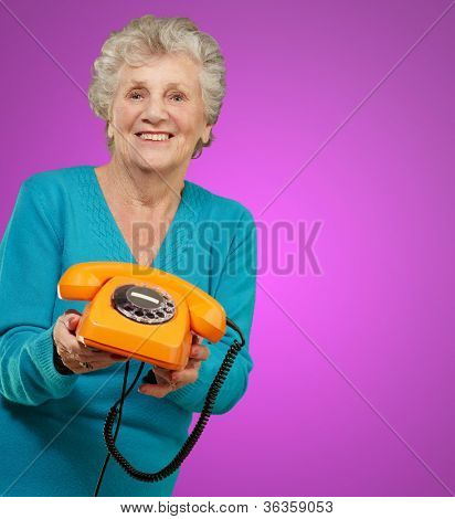 Mature Happy Woman Holding Telephone On Purple Background