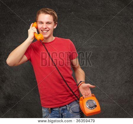 retrato de jovem falando com telefone vintage contra uma parede de grunge
