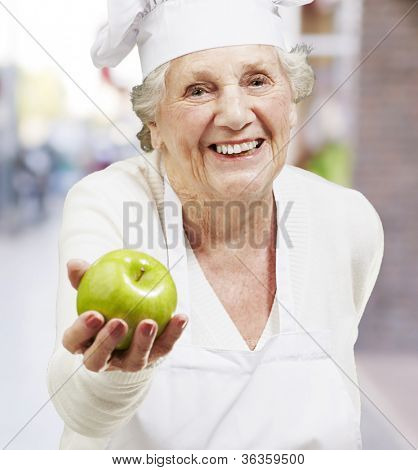 senior woman cook offering a green apple against a street background