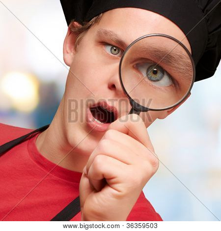 portrait of young cook man looking through a magnifying glass indoor