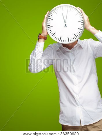 Young Man Holding Big Clock Covering His Face On Green Background
