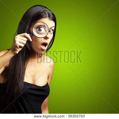 portrait of young woman surprised looking through a magnifying glass over green