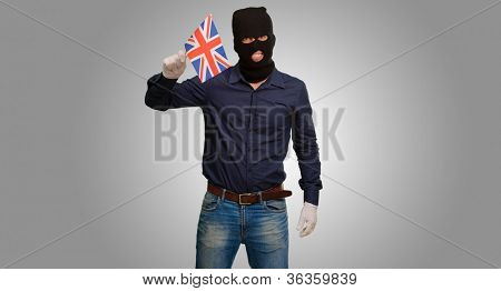 Portrait of a man wearing mask holding a flag isolated on grey background