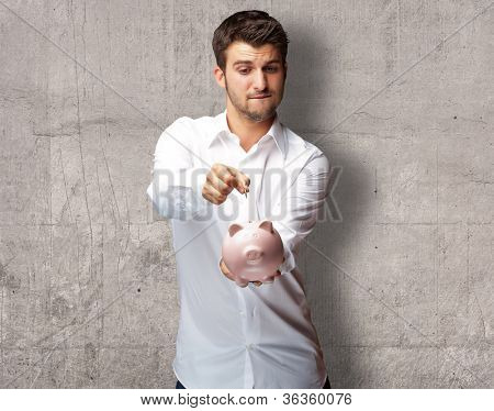 A Businessman Putting A Coin Into A Pink Piggy Bank, Indoor