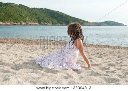 little girl lookin a sea landescape