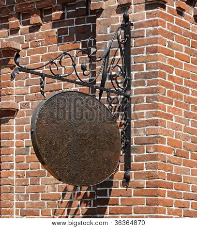Blank, dark, shop sign hanging in a wrought iron bracket from a brick wall