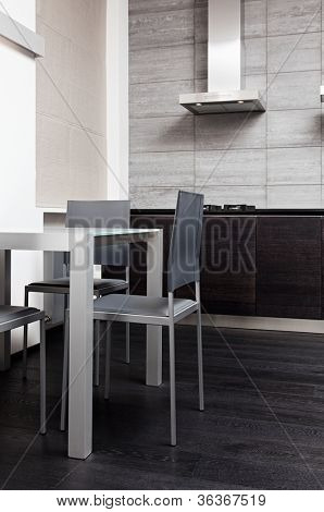 Fragment of modern minimalism style kitchen with dining table