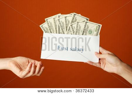 Woman's hand passes the envelope with the salary on brown background