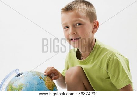 Little boy with globe, looking at camera