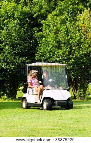 Junges sportliches paar Golf auf einem Golfplatz zu spielen, fahren sie mit Golf-cart
