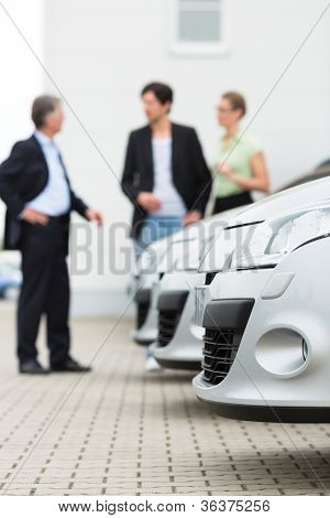 Two men man and one woman stand behind a row of silver-metallic cars on a parking place on yard of dealer