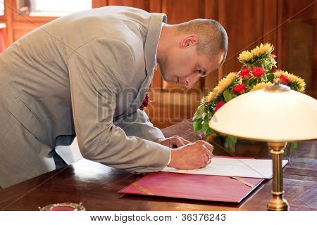 Groom signing marriage form