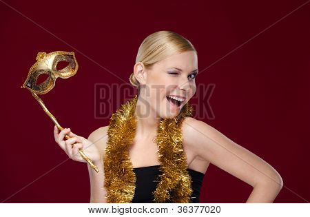 Pretty girl with masquerade mask and tinsel, isolated on purple