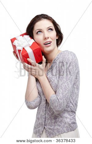 Young woman applies her ear to the present wrapped in red paper, isolated on white