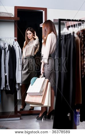 Woman admires herself at the mirror in the store after shopping