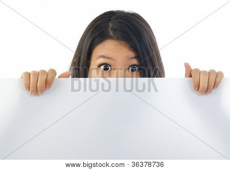 Shock Asian woman open eyes big, hiding behind a white card and covering mouth.