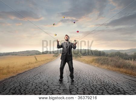 Young businessman juggling on a country road