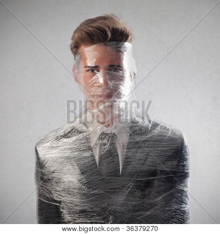 Young businessman packed in plastic wrap