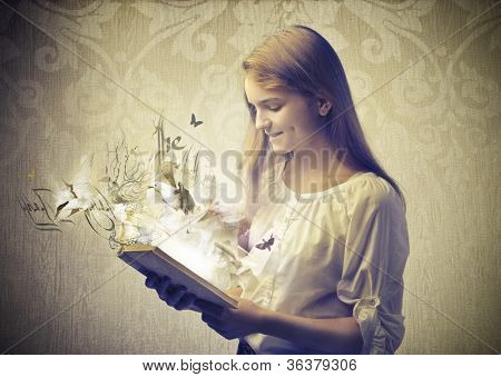 Smiling teenage girl reading a book with birds coming out from it