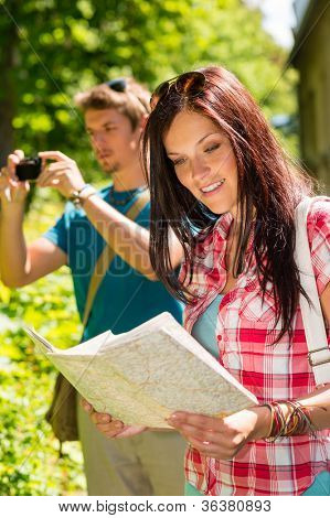 Young tourist couple travel holiday with map and photographing camera