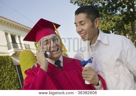 Happy senior male graduate on call with son looking at him