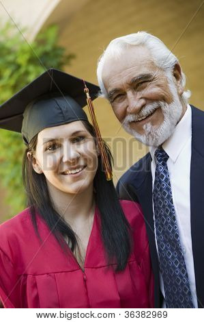 Portrait of a young female graduate with grandfather smiling