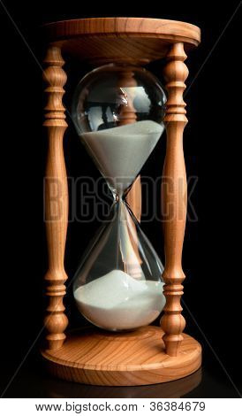 Sand flowing inside of hourglass against a black background