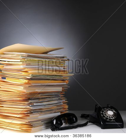 A large stack of files on a desk and a retro style telephone with the receiver off the hook. Square format over a light to dark gray background.