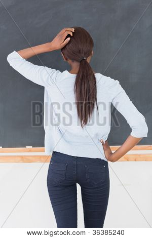 Black woman thinking in front of a blackboard in a classroom