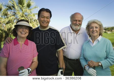 Group portrait of multiethnic golfers standing together
