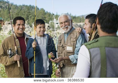 Happy Hispanic senior man with sons and grandson on a fishing trip