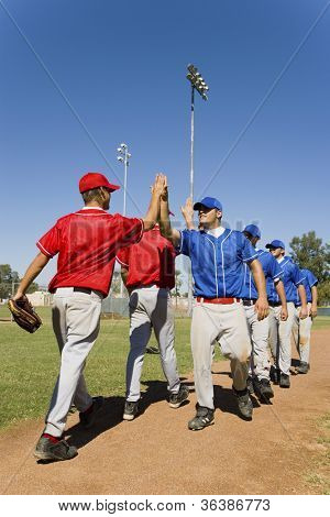 Baseball players giving high-five to each other after match